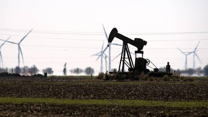 An oil pump jack in a field with wind turbines in Corpus Christi, Texas, U.S., Friday, Feb. 19, 2021.