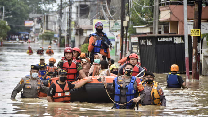 Rescuers evacuate residents from their flooded homes in Bekasi on February 19, 2021, as heavy rain inundated the city on the outskirts of Jakarta.
