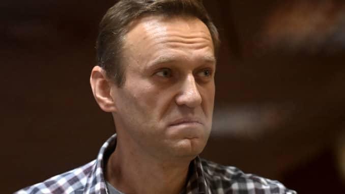 Pemimpin oposisi Rusia Alexei Navalny berdiri di dalam sel kaca selama sidang di pengadilan distrik Babushkinsky di Moskow pada 20 Februari 2021.