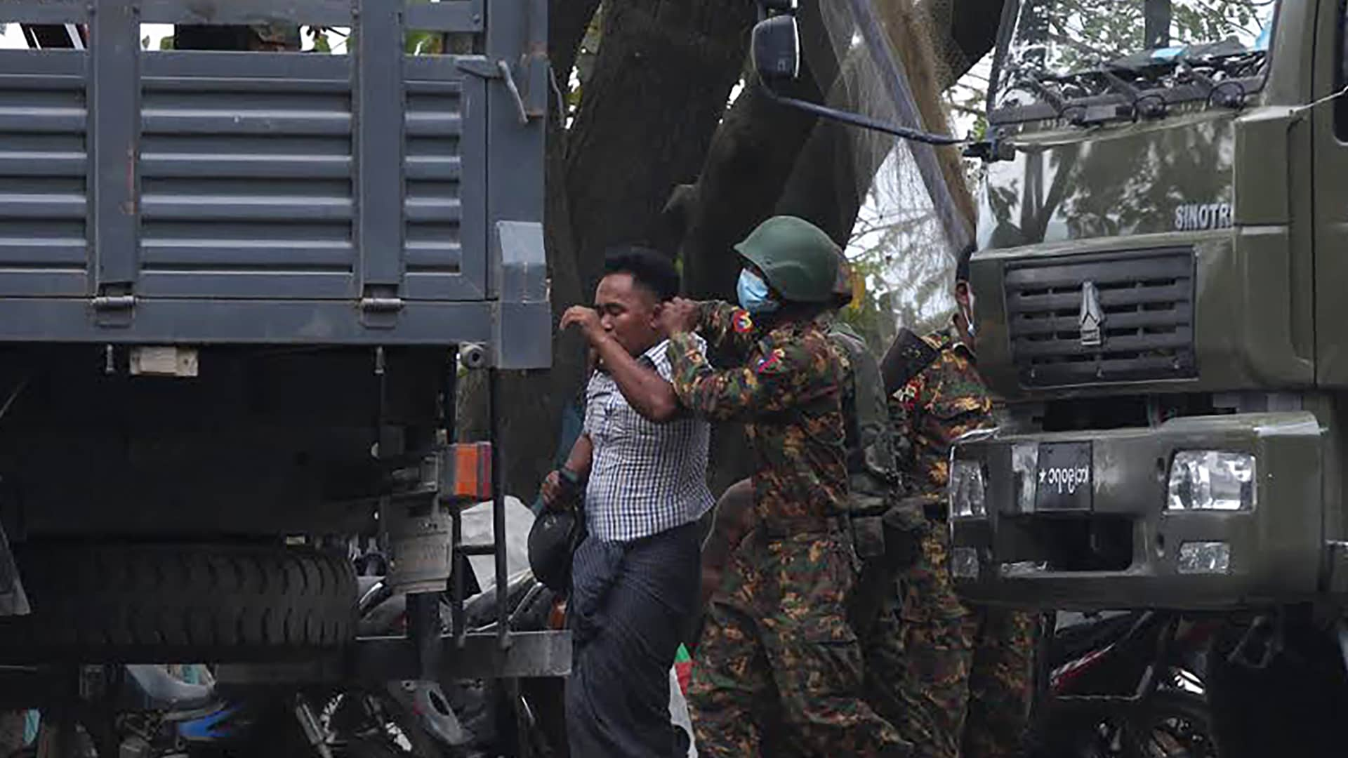 A protester is led away after being detained by security forces during a demonstration against the military coup in Mandalay on February 20, 2021.