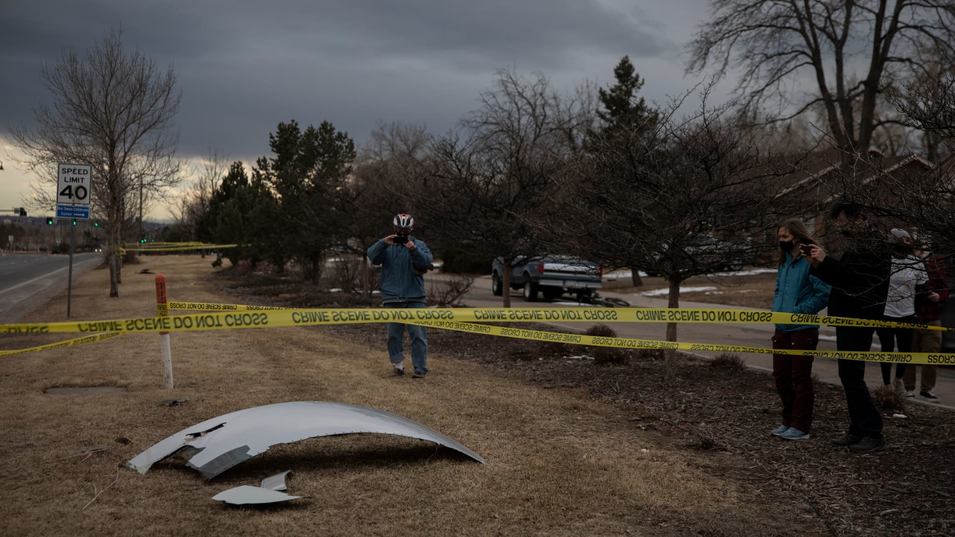 Residents take pictures of debris fallen from a United Airlines airplane's engine on the neighborhood of Broomfield, outside Denver, Colorado, on Feb. 20, 2021. A United Airlines flight suffered a fiery engine failure Feb. 20, shortly after taking off from Denver on its way to Hawaii, dropping massive debris on a residential area before a safe emergency landing, officials said.