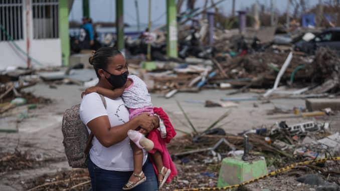 Seorang warga yang menggendong seorang anak berjalan melewati puing-puing dari rumah yang rusak setelah Badai Iota menghantam Pulau Providencia, Kolombia, pada Sabtu, 21 November 2020.