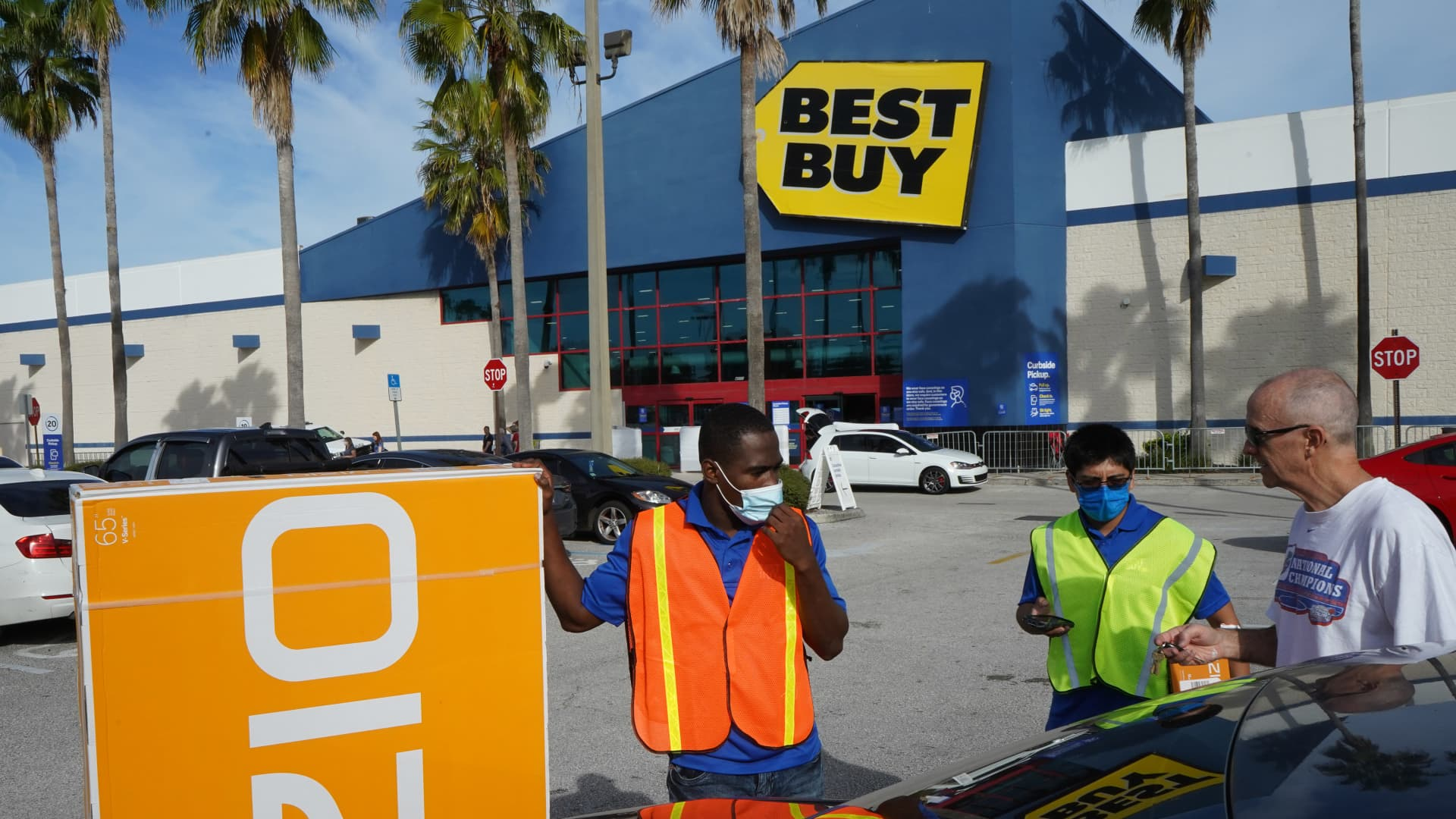 Employees bring a television to Steve Steward's car at a Best Buy store on Black Friday, traditionally one of the busiest shopping days of the year. Crowds are smaller this year due to the increasing popularity of on-line shopping amid concerns about the COVID-19 pandemic.
