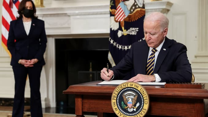 U.S. President Joe Biden signs an executive order, aimed at addressing a global semiconductor chip shortage, as Vice President Kamala Harris stands by in the State Dining Room at the White House in Washington, February 24, 2021.