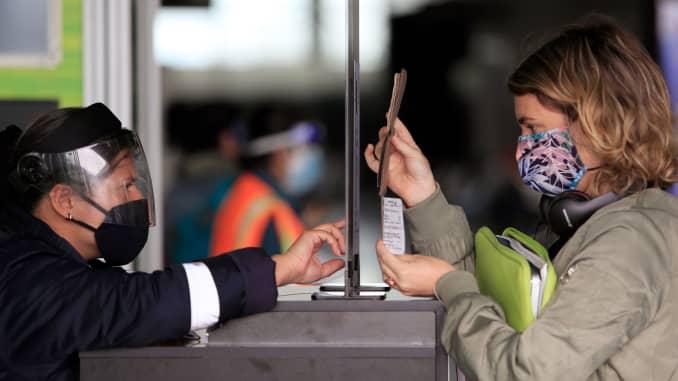 Seorang penumpang yang menggunakan masker wajah menunjukkan paspor dan boarding passnya kepada seorang karyawan di pos pemeriksaan keamanan di Bandara Internasional El Dorado di Bogota pada 1 September 2020.