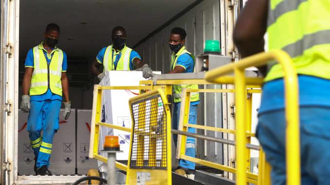 Pekerja bandara membongkar pengiriman vaksin Covid-19 dari program vaksinasi global Covid-19 Covax, di Bandara Internasional Kotoka di Accra, pada 24 Februari 2021.