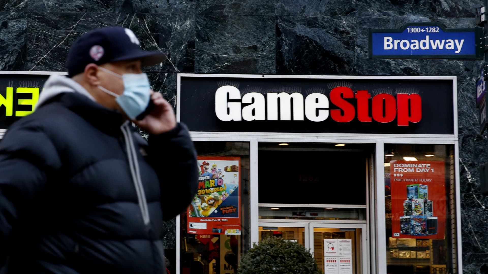 A man talks by his phone in front of GameStop at 6th Avenue on February 25, 2021 in New York.