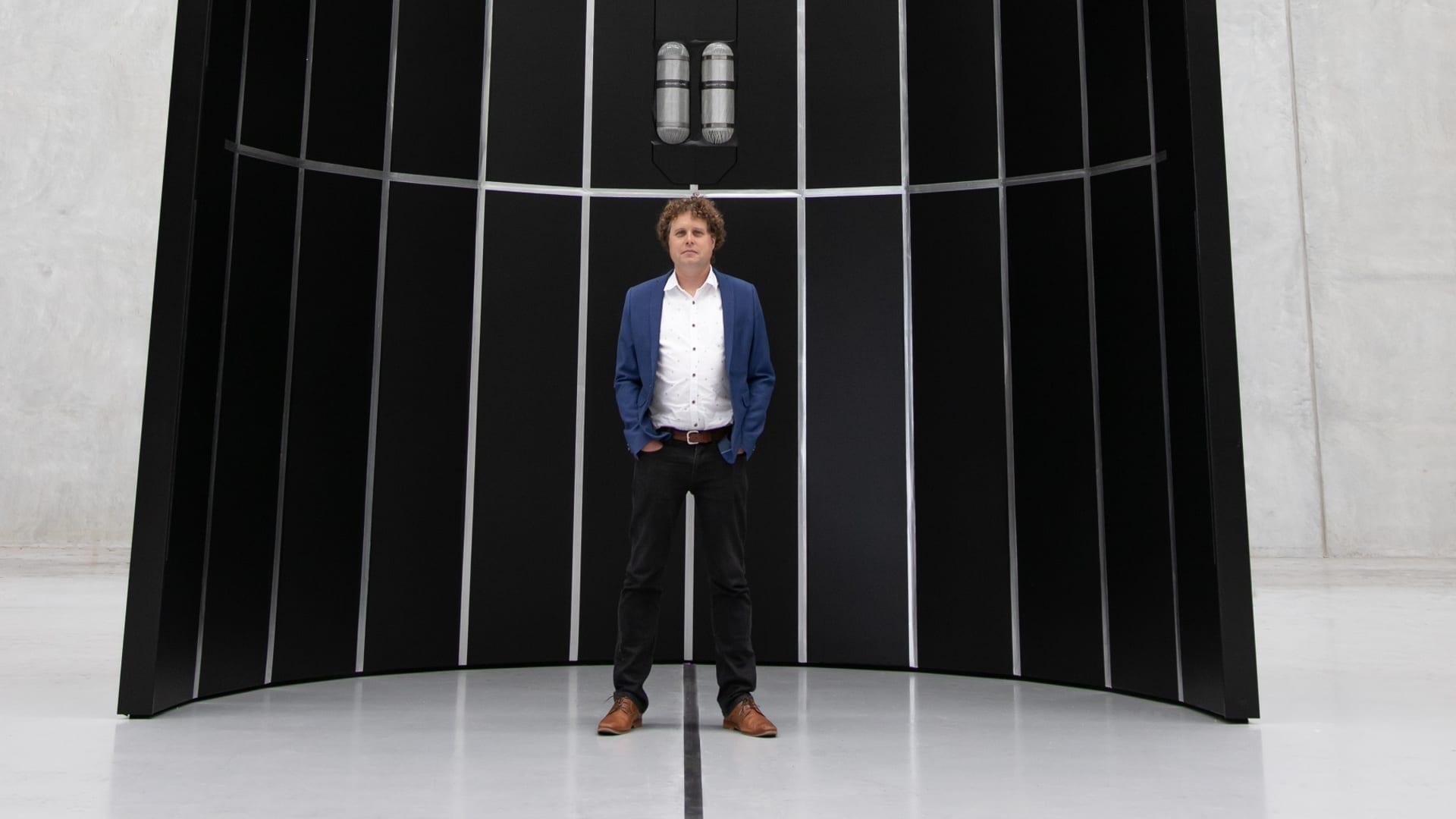 CEO Peter Beck stands at the base of the fairing, or nosecone, of the Neutron rocket the company is developing.