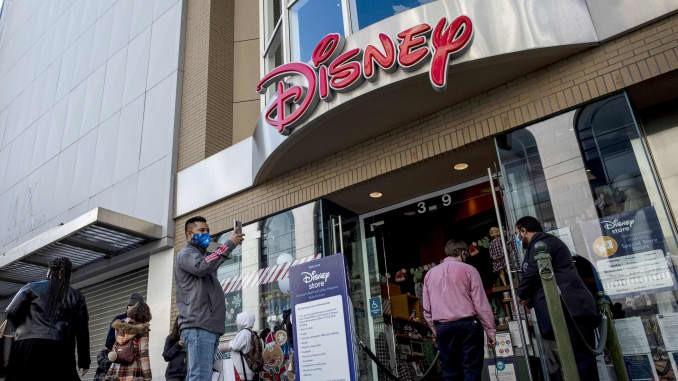 Pedestrians wearing protective masks wait to enter a Disney store in San Francisco, California, on Wednesday, Dec. 23, 2020.