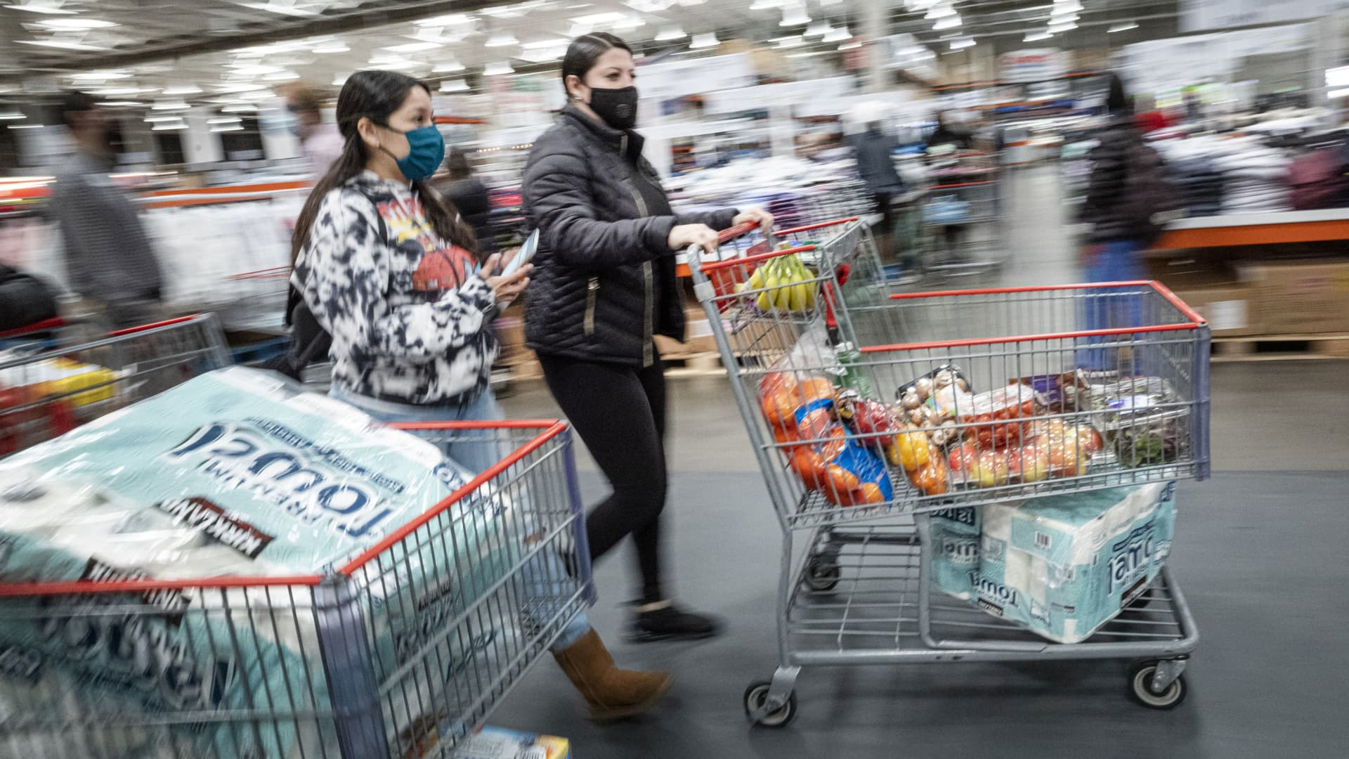 Shoppers wearing protective masks push shopping carts inside a Costco store in San Francisco, California, on Wednesday, March 3, 2021.