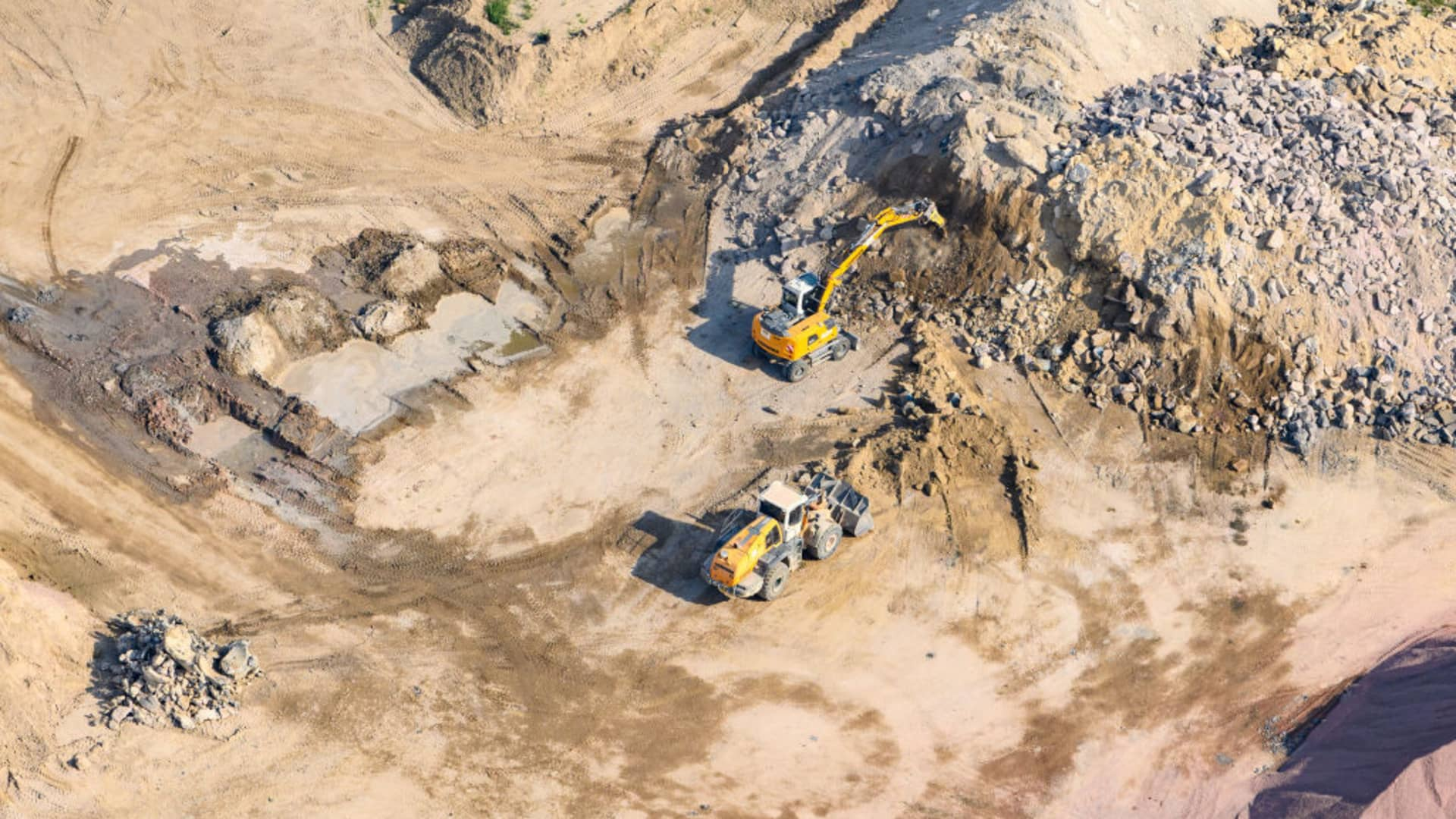 An excavator and a bulldozer are working on the grounds of the gravel plant and the concrete mixing plant of the Max Bögl group of companies.