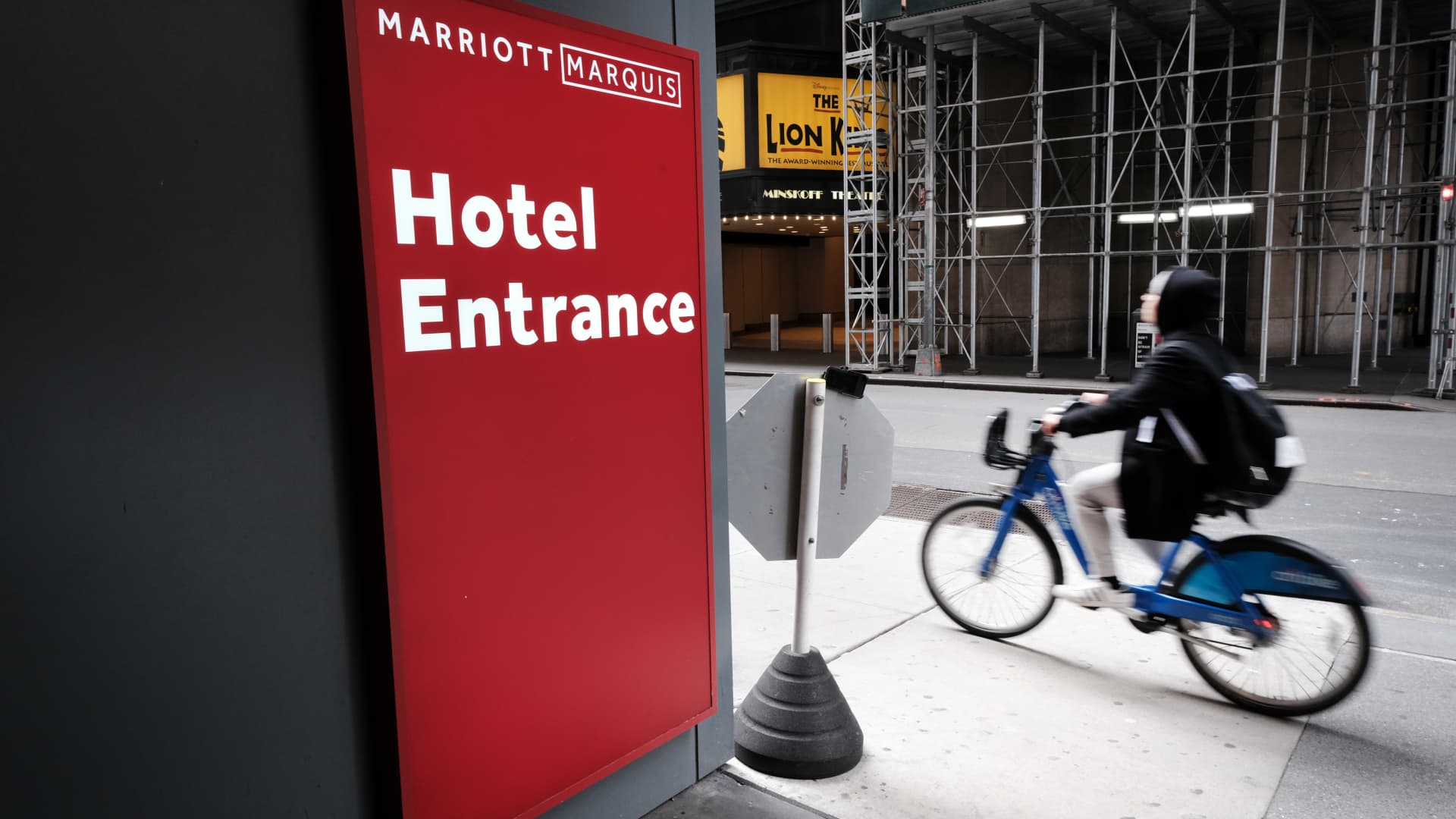 A person rides a bike past the Marriott hotel in Times Square, New York.