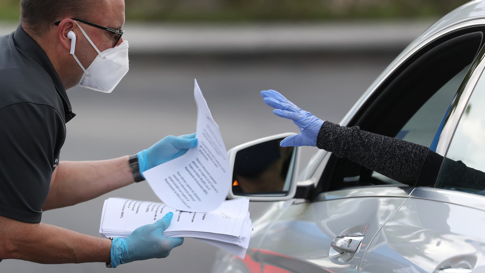 Eddie Rodriguez, who works for the City of Hialeah, hands out unemployment applications to people in their vehicles on April 8, 2020 in Hialeah, Florida.