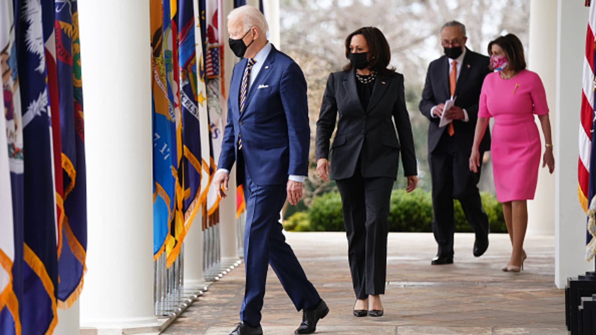 President Joe Biden, from left, U.S. Vice President Kamala Harris, Senate Majority Leader Chuck Schumer, a Democrat from New York, and U.S. House Speaker Nancy Pelosi, a Democrat from California, wear protective masks while arriving to an event in the Rose Garden of the White House in Washington, D.C., on Friday, March 12, 2021.