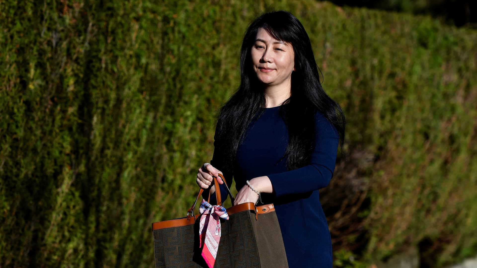 Huawei Technologies Chief Financial Officer Meng Wanzhou reaches into her bag for a face mask as she leaves her home to attend a court hearing in Vancouver, British Columbia, Canada March 15, 2021.