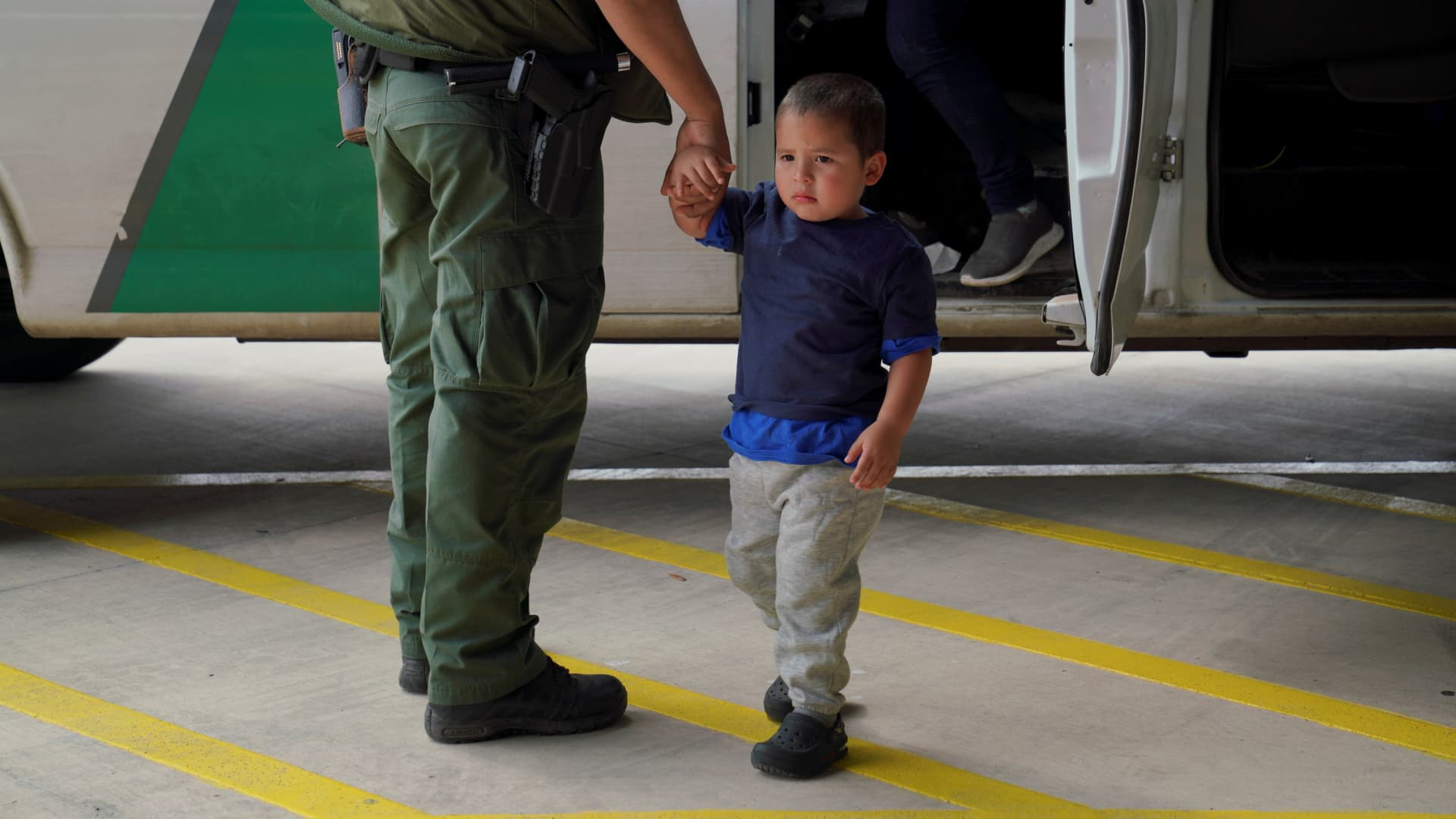 A Border Patrol agent holds an asylum-seeking child as his mother gets off the vehicle at the bus station after being processed through immigration in Brownsville, Texas, U.S. March 15, 2021.