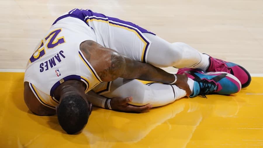 Penyerang Los Angeles Lakers LeBron James memegang pergelangan kakinya setelah mengalami cedera pada paruh pertama pertandingan bola basket NBA melawan Atlanta Hawks, Sabtu, 20 Maret 2021, di Los Angeles