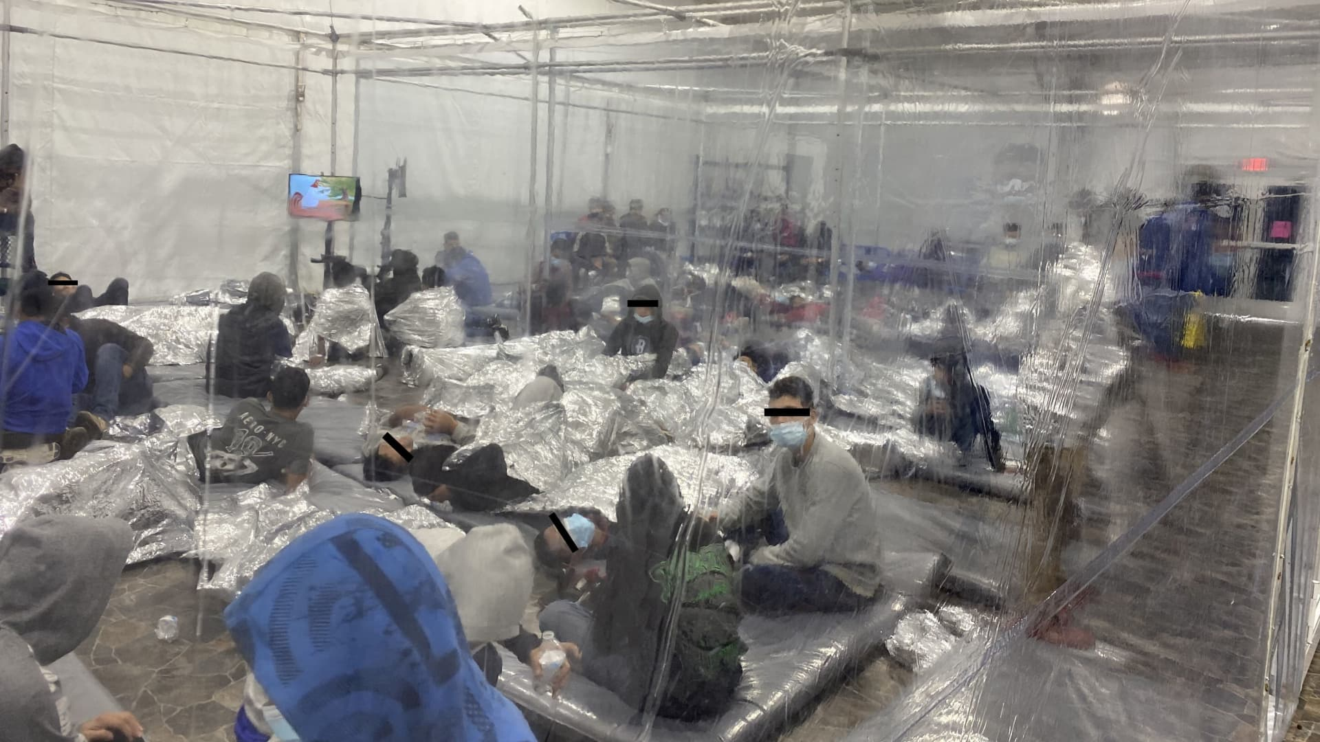 Migrants crowd a room with walls of plastic sheeting at the U.S. Customs and Border Protection temporary processing center in Donna, Texas, U.S. in a recent photograph released March 22, 2021.