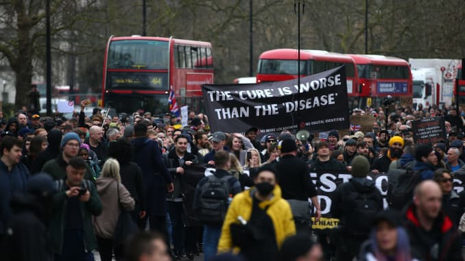 """Protesters carry a sign saying """"The 'cure' is worse than the 'disease'"""" as they march during a """"World Wide Rally For Freedom"""" protest on March 20, 2021 in London, England."""