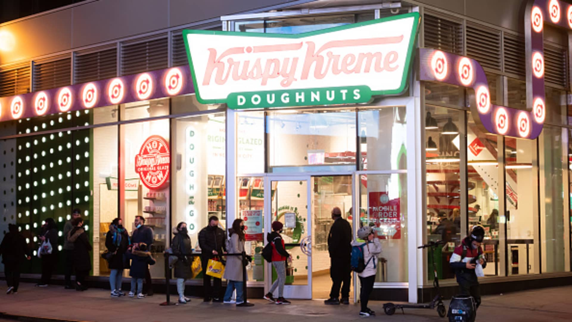 People line up outside Krispy Kreme in Times Square amid the coronavirus pandemic on March 17, 2021 in New York City. After undergoing various shutdown orders for the past 12 months the city is currently in phase 4 of its reopening plan, allowing for the reopening of low-risk outdoor activities, movie and television productions, indoor dining as well as the opening of movie theaters, all with capacity restrictions.