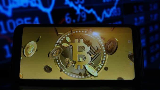 Trong hình minh họa này, một biểu tượng Bitcoin được nhìn thấy hiển thị trên điện thoại thông minh với tỷ lệ phần trăm thị trường chứng khoán trong nền.
