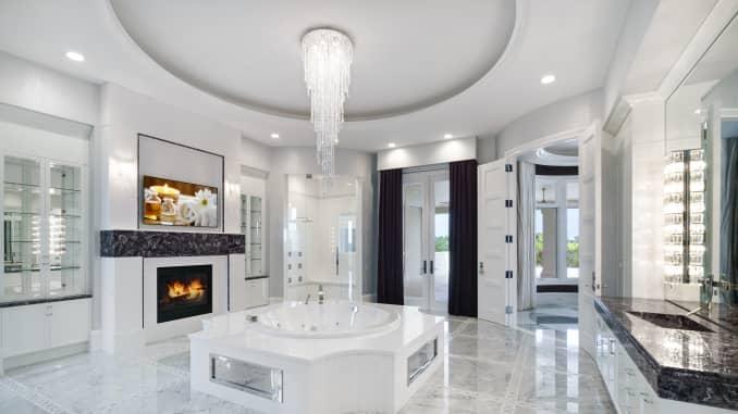 Phòng tắm của cô với lò sưởi, bồn tắm nước nóng và các điểm nhấn bằng Thạch anh tím.