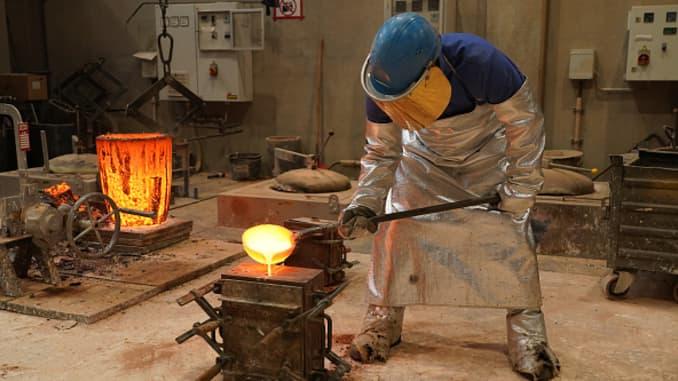 Một công nhân đổ đồng nóng chảy vào khuôn để đúc cúp gấu Berlinale ở Berlin, Đức.