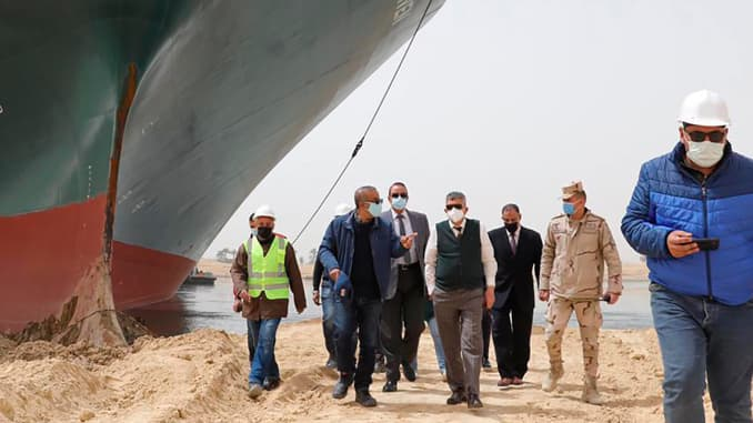 Lt. Gen. Ossama Rabei, center, head of the Suez Canal Authority, with a team walk along the bank of the Suez Canal where the Ever Given, a Panama-flagged cargo ship, has become wedged across the Suez Canal and blocking traffic in the vital waterway. An op