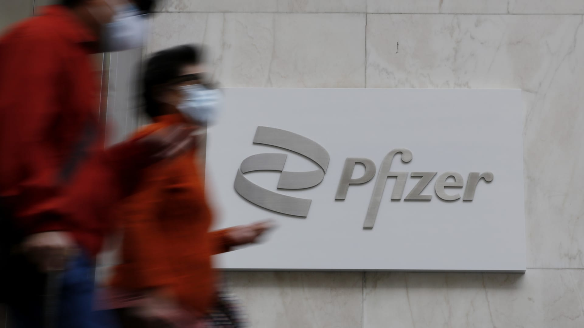 People walk in front of Pfizer sign at Pfizer World Headquarters on March 23, 2021 in New York. The Food and Drug Administration (FDA) says Pfizer's coronavirus vaccine can be stored in normal freezers for two weeks, instead of storage at ultra-cold temperatures.