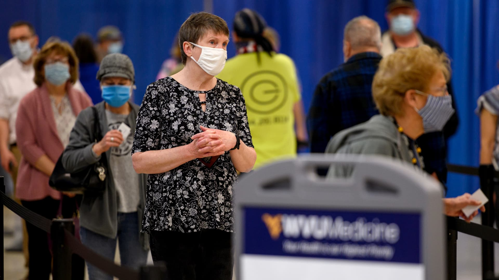 Residents wear protective masks while waiting to be vaccinated at a West Virginia United Health System Covid-19 vaccine clinic in Morgantown, West Virginia, U.S., on Thursday, March 11, 2021.