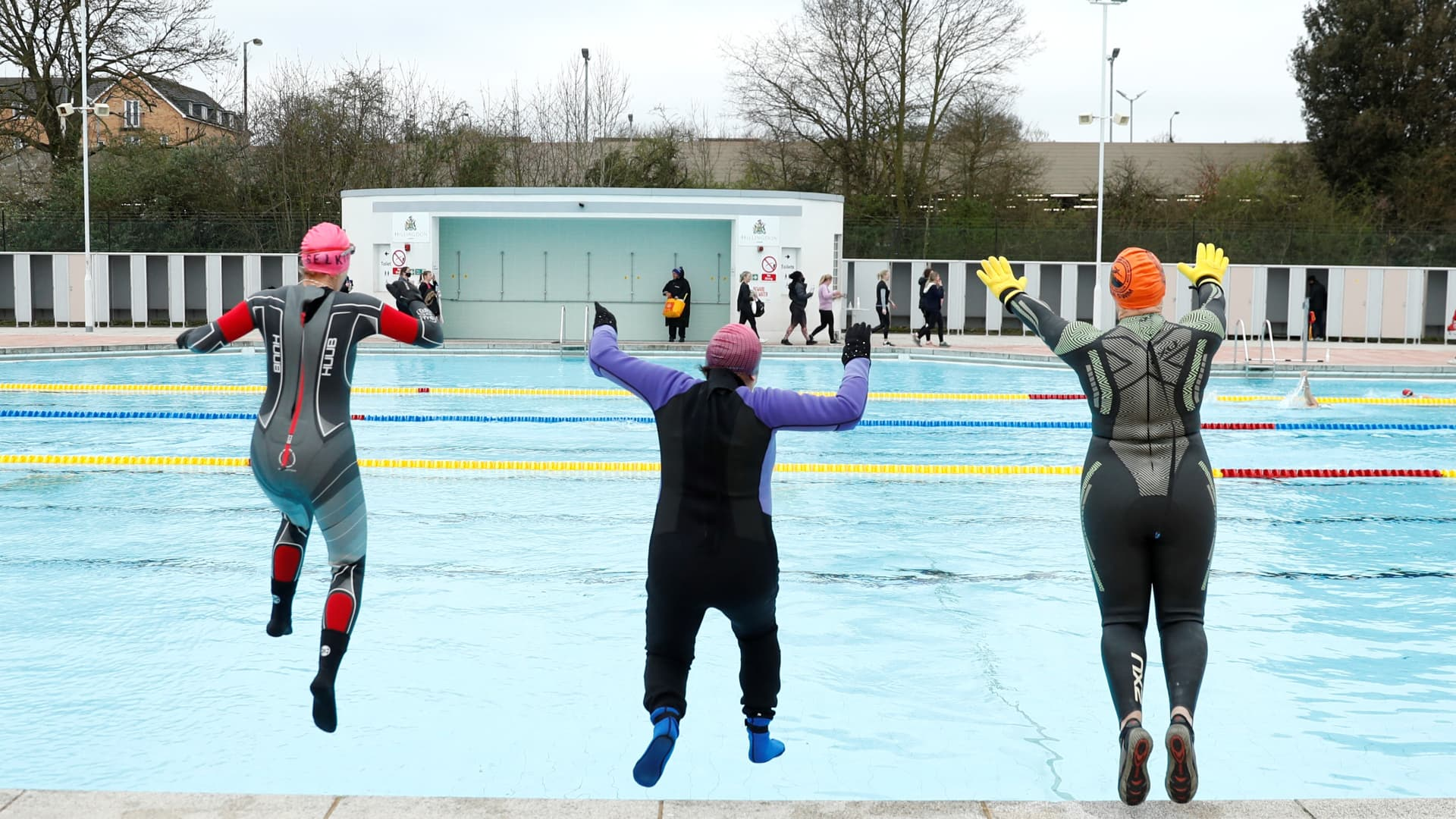Swimmers jump into the water at Hillingdon lido in west London as England's third Covid-19 lockdown restrictions ease, allowing outdoor sports facilities to open on March 29, 2021.