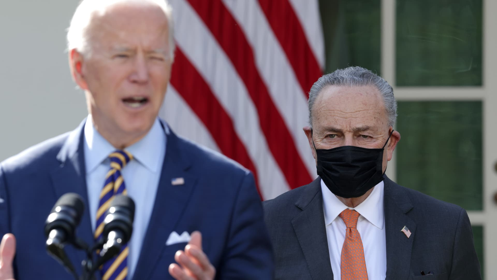Senate Majority Leader Sen. Chuck Schumer (D-NY) (R) listens as U.S. President Joe Biden speaks during an event on the American Rescue Plan in the Rose Garden of the White House on March 12, 2021 in Washington, DC.