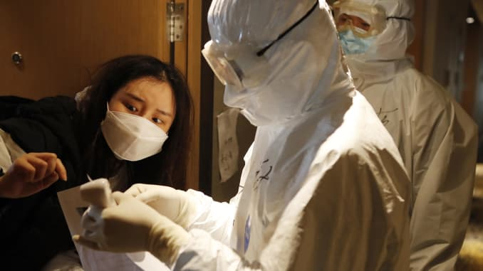 A staff member checks information of a woman who just finishes her quarantine at a quarantine center on March 16, 2020 in Shanghai, China.