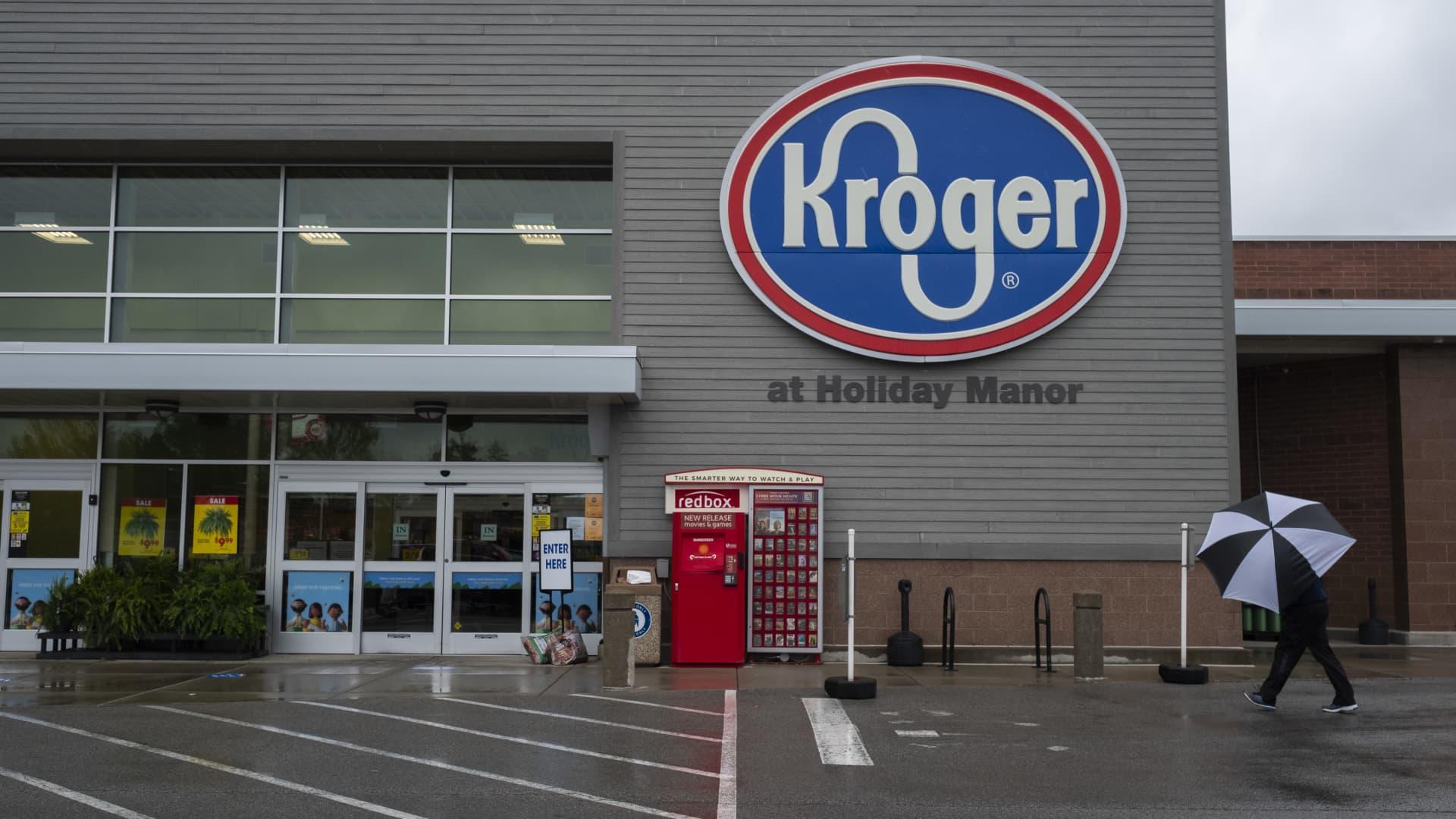 A shopper holding an umbrella walks towards a Kroger Co. grocery store in Louisville, Kentucky, U.S., on Sunday, April 26, 2020.