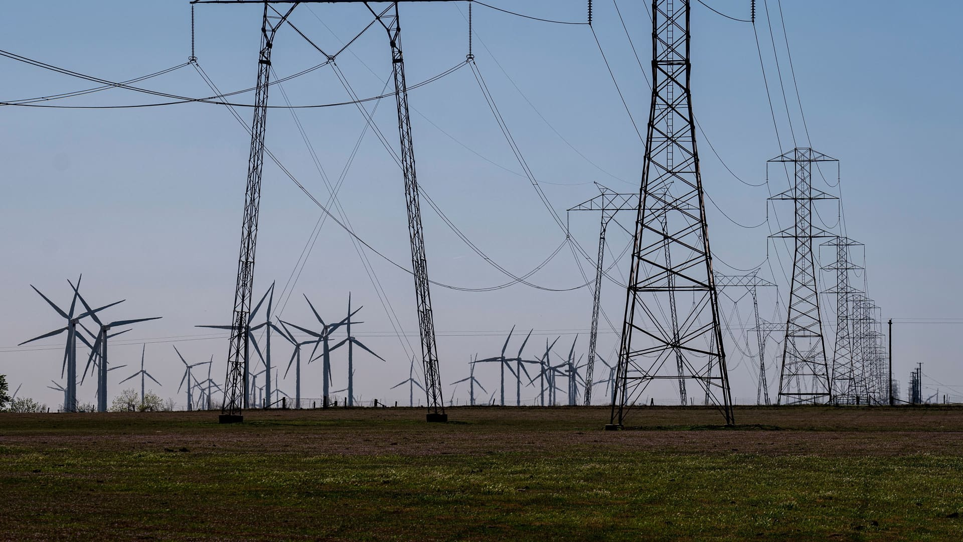 Wind turbines and power transmission lines at a wind farm near Highway 12 in Rio Vista, California, on Tuesday, March 30, 2021.