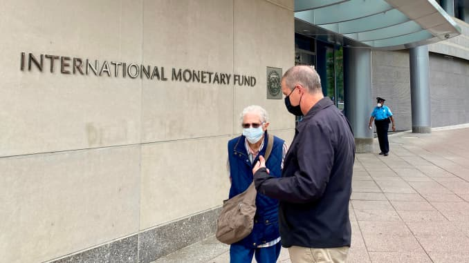 People are talking in front of the International Monetary Fund (IMF) building in Washington DC on September 25, 2020.