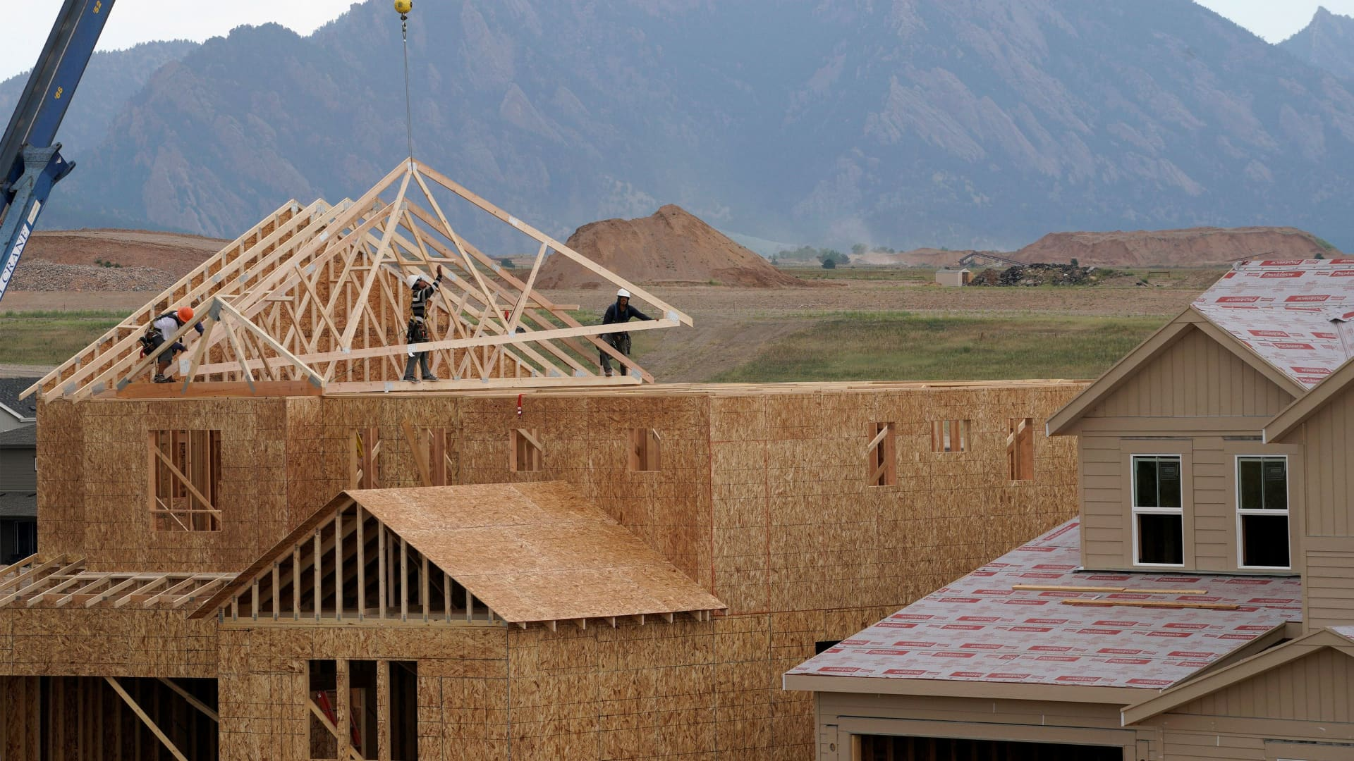 Workers install roof trusses onto a new house in Arvada, Colorado.