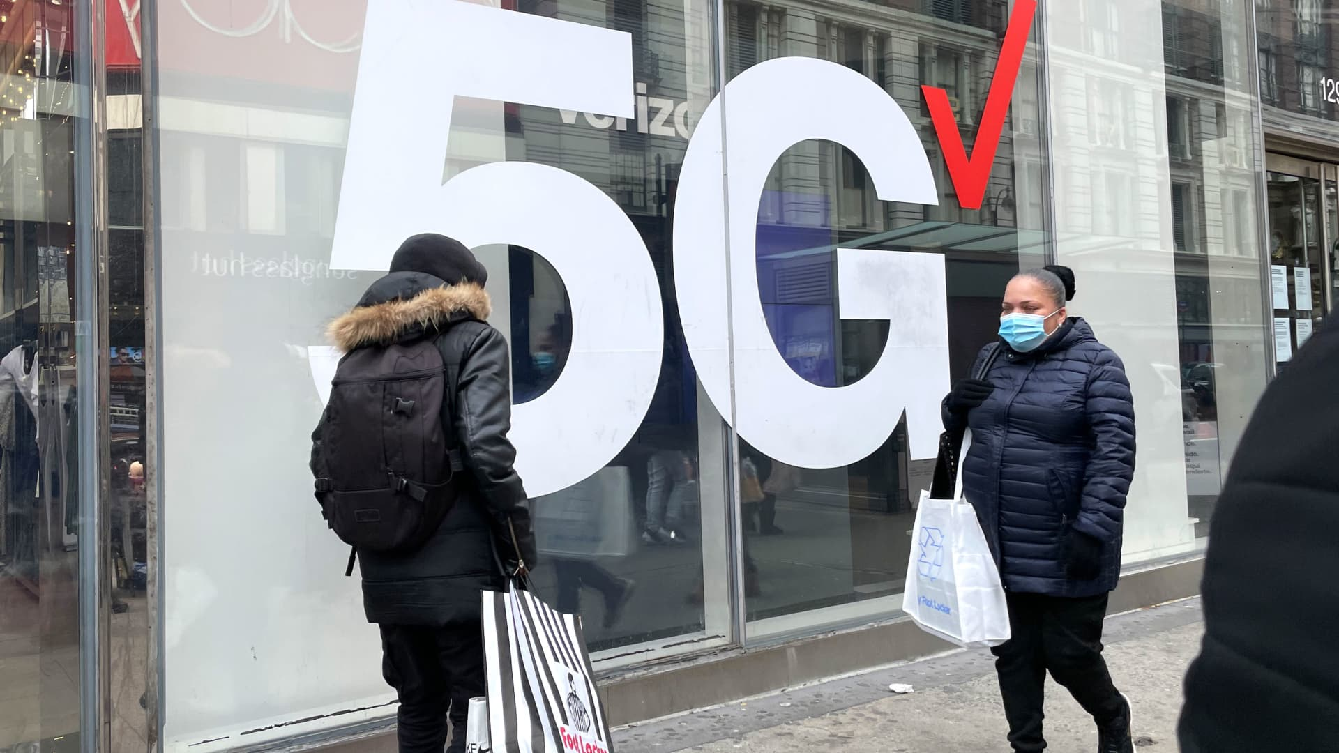 Pedestrians walk by a Verizon 5G sign in New York, April 3, 2021.