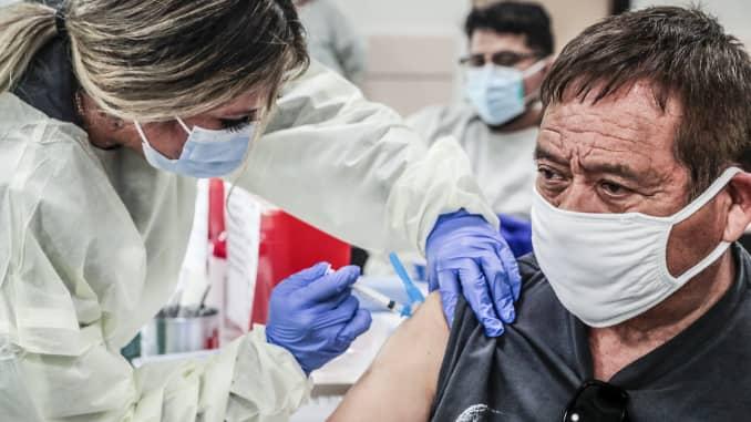 Kỹ thuật viên y tế Janette Serrano tiêm cho Henry Perez, 71 tuổi, một loại vắc-xin Covid-19 được cung cấp tại Trung tâm Cộng đồng Bell.