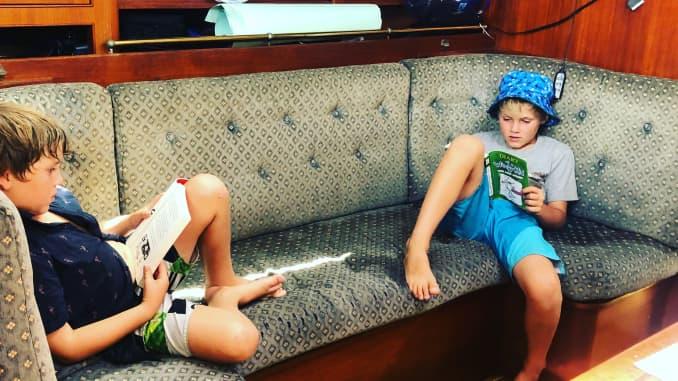 Hai chàng trai trẻ thư giãn trên ghế sofa trên chiếc thuyền mà họ sống.
