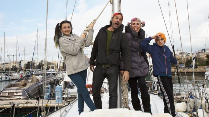 Một gia đình đi du lịch toàn thời gian đứng trên một chiếc thuyền.