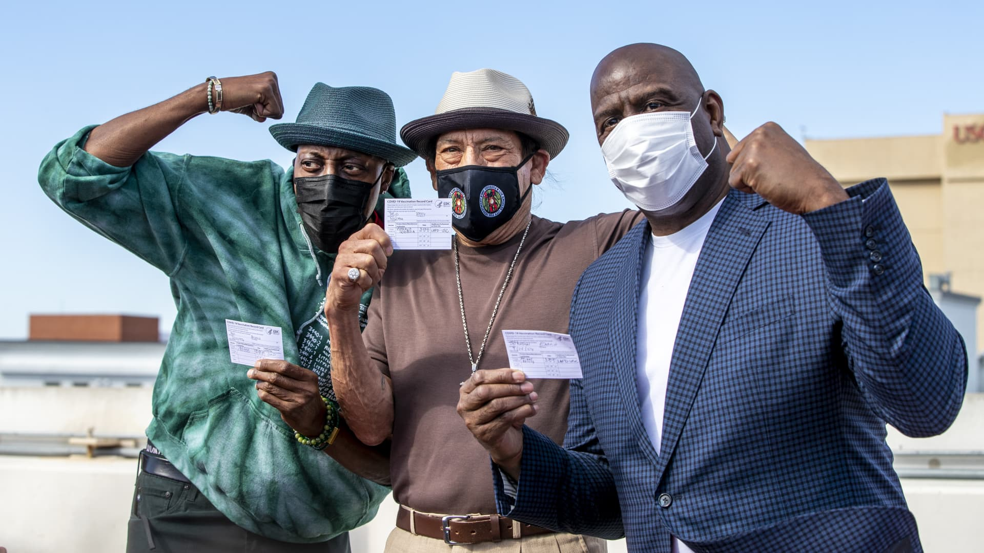 Arsenio Hall, left, Danny Trejo and Magic Johnson pose for a photo after they all got vaccine shots on the rooftop of parking structure at USC as a part of a vaccination awareness event at USC on March 24, 2021 in Los Angeles, California.