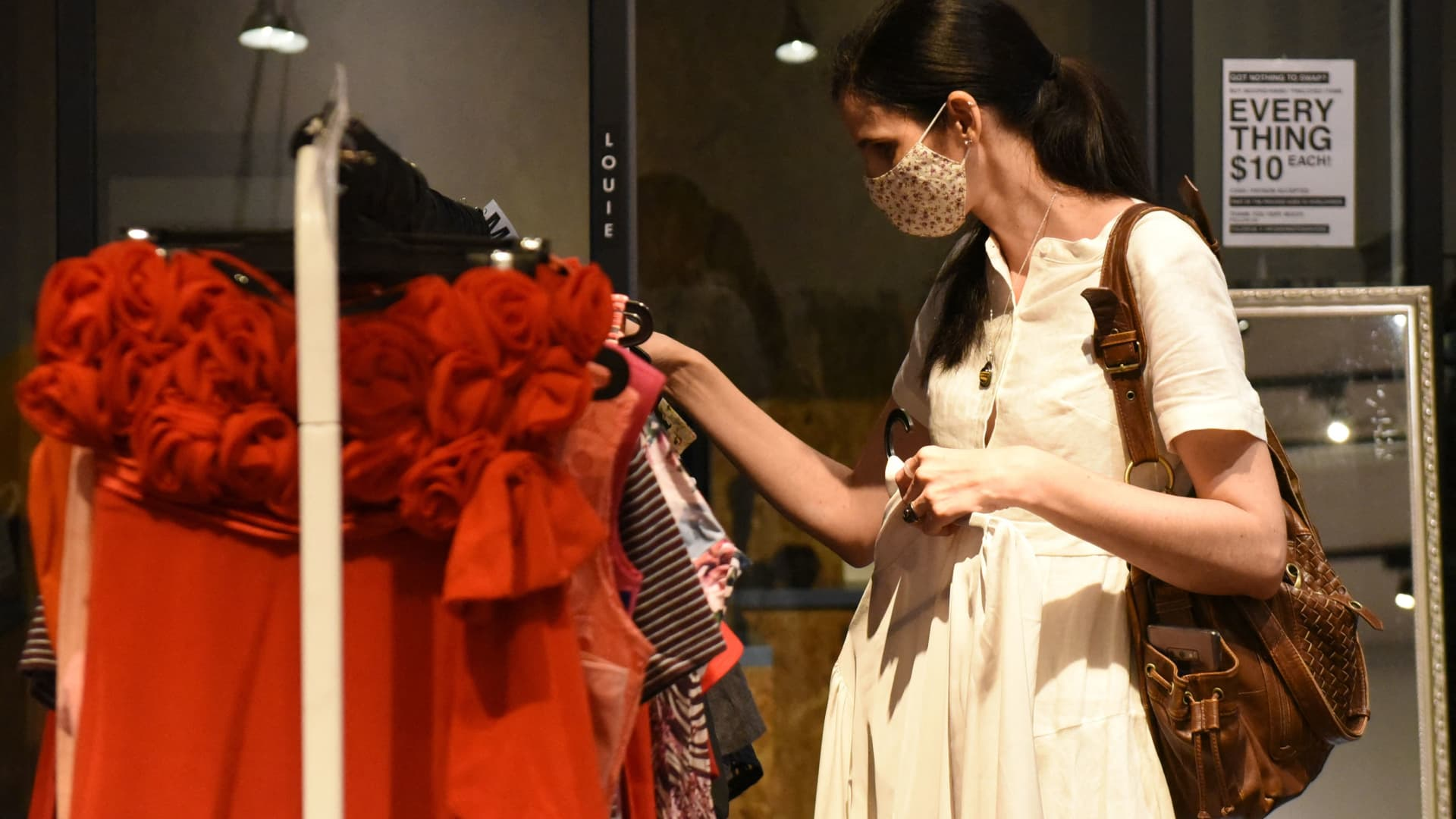 A shopper browsing through secondhand clothes at a pop-up swap event in Singapore.