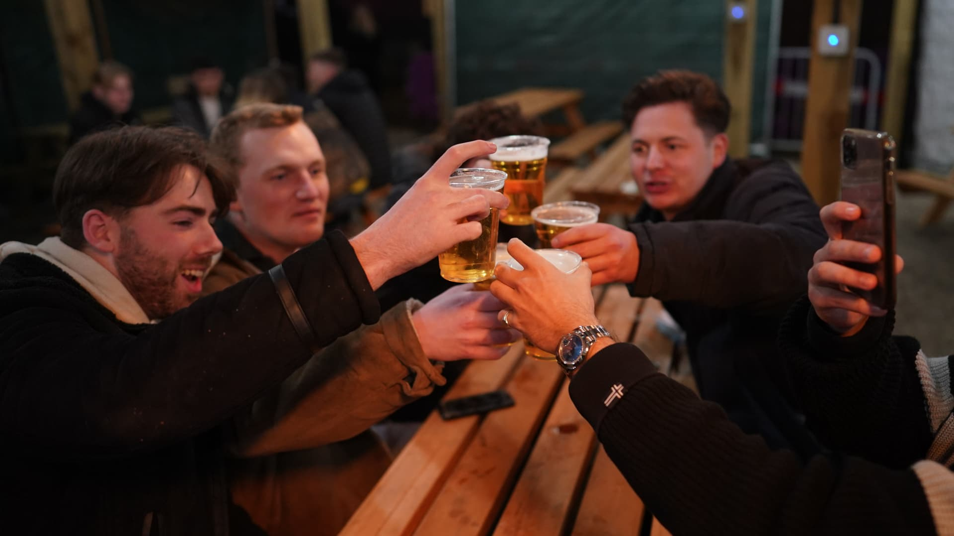 Friends make a toast as they enjoy a drink at the Switch bar in Newcastle shortly after midnight following the easing of lockdown measures on April 12, 2021 in Newcastle Upon Tyne, England.