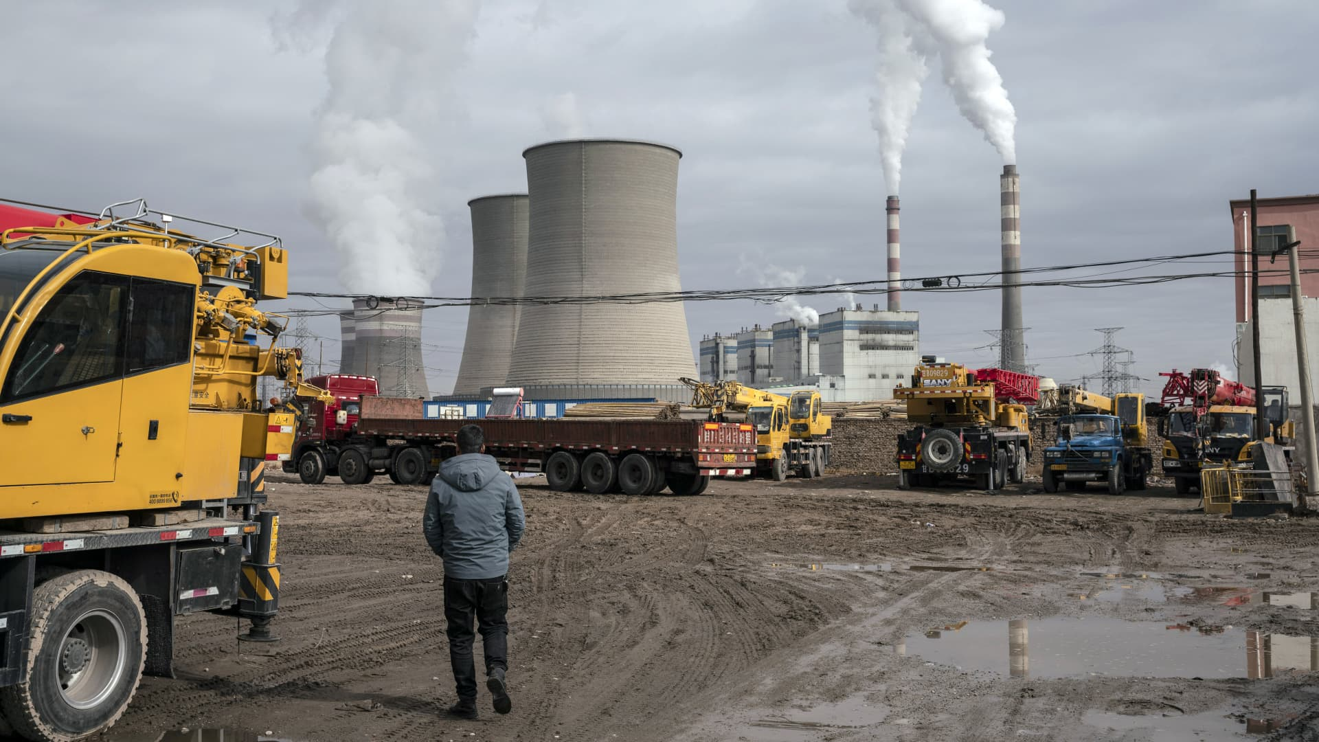 A person walks past a coal fired power plant in Jiayuguan, Gansu province, China, on Thursday, April 1, 2021.