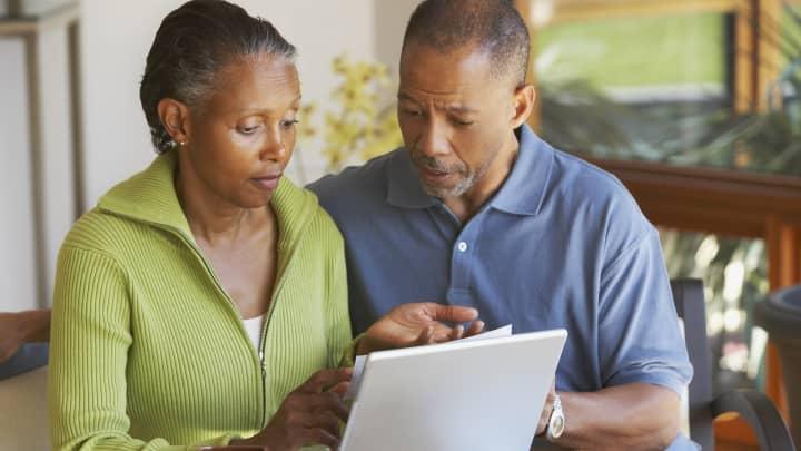 GP: Senior African American couple paying bills
