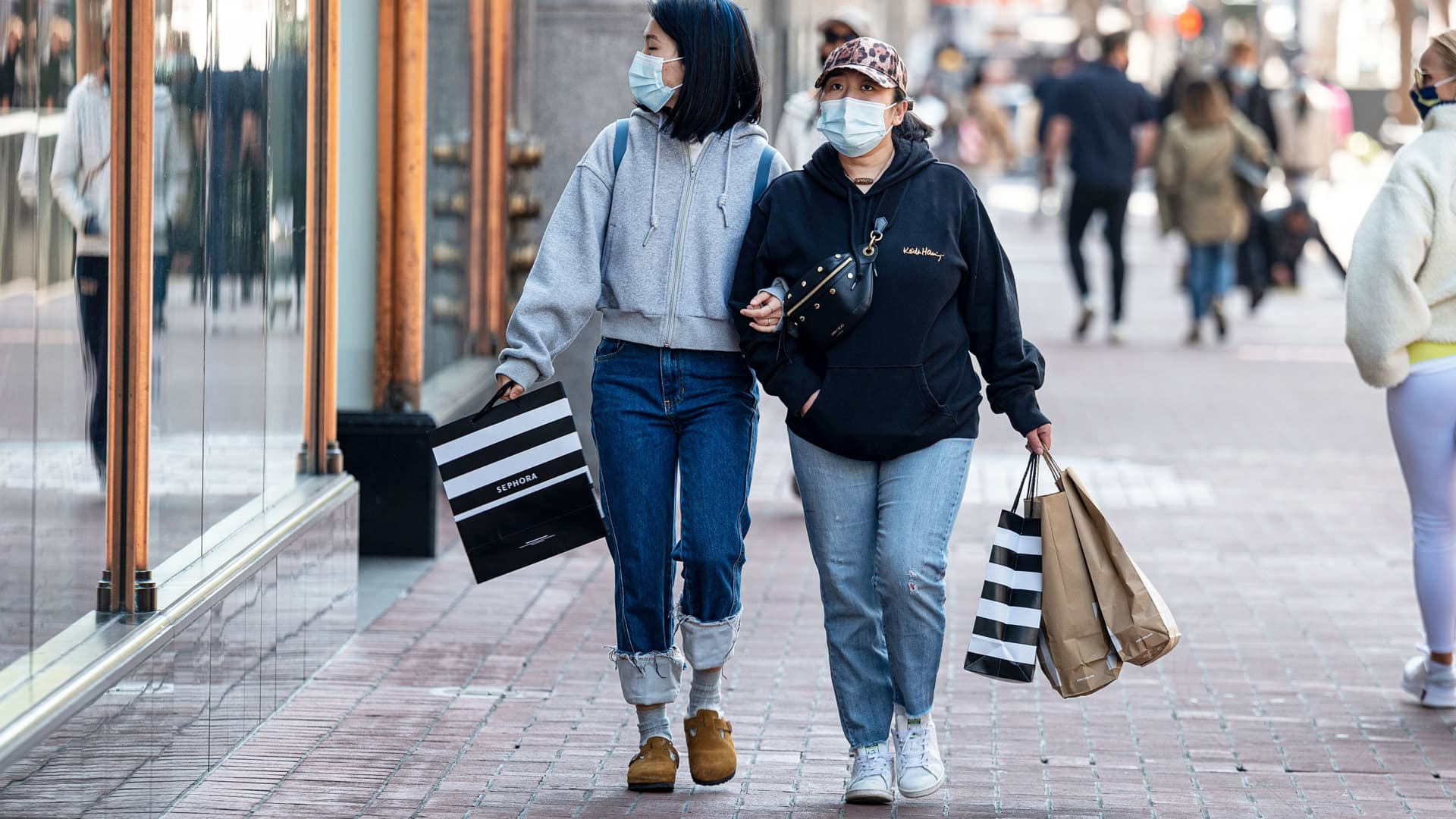 Shoppers wearing protective masks carry bags on Market Street in San Francisco, California, on Wednesday, April 14, 2021.