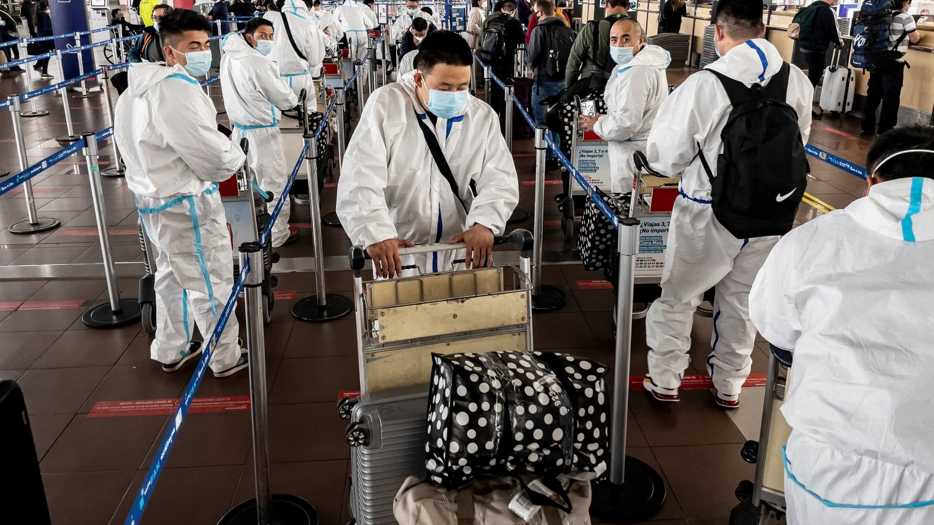 Passengers in protective suits against the spread of the novel coronavirus disease, queue at counters at Arturo Merino Benitez International Airport in Santiago on April 1, 2021, after Chile announced it will close its borders in April as of Monday amid a surge in COVID-19 cases.