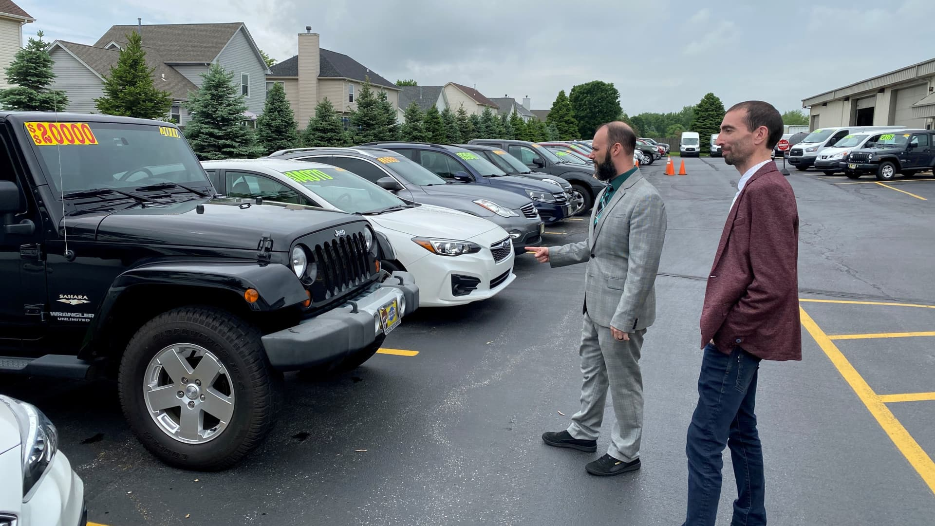 Alex Tovstanovsky, owner of used-car dealer Prestige Motor Works, checks on inventory with his general manager Ryan Caton in Naperville, Illinois, May 28, 2020.