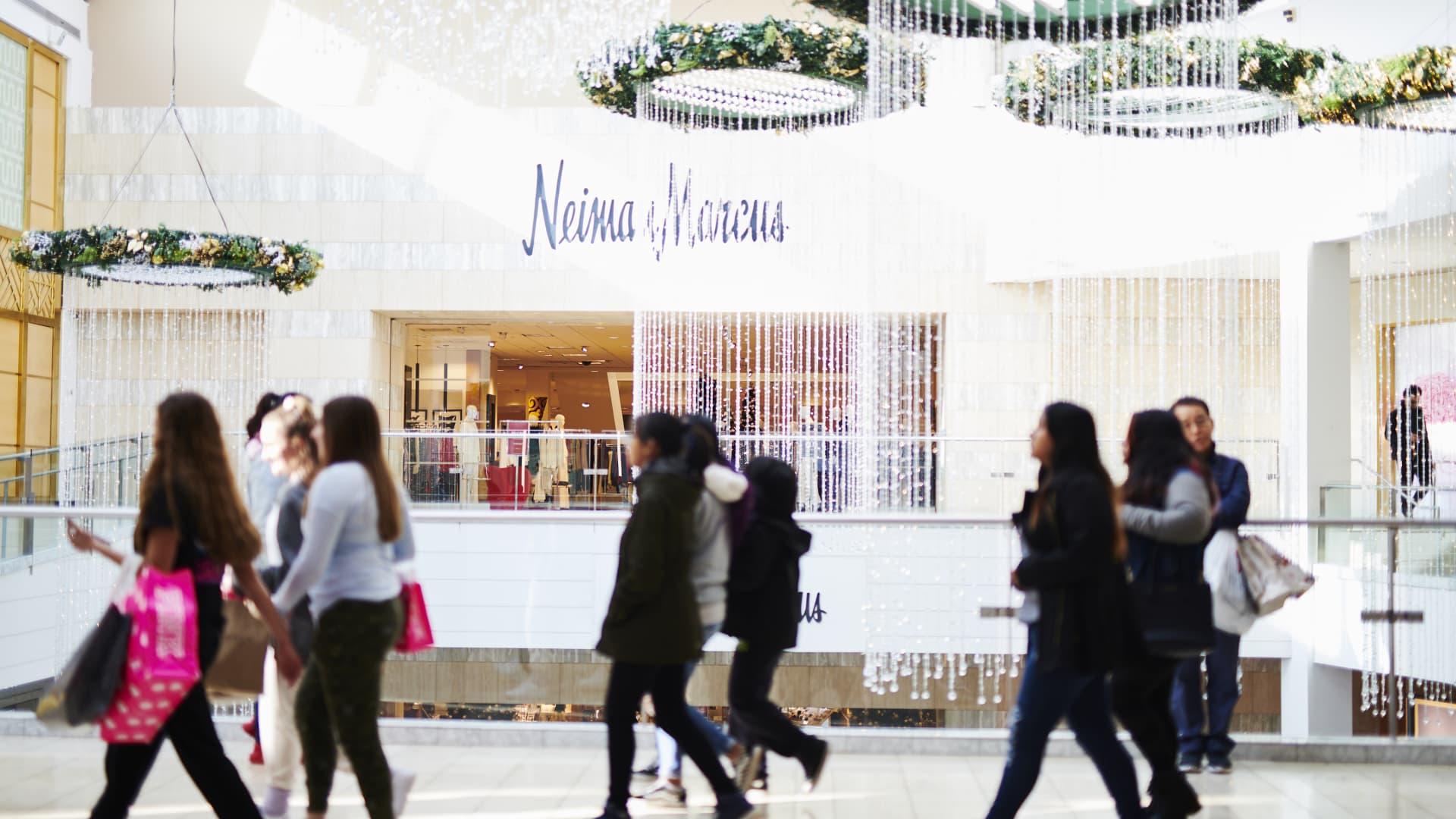 Shoppers pass in front of a Neiman Marcus Group Inc. store at the Westfield Garden State Plaza mall on Black Friday in Paramus, New Jersey, U.S., on Friday, Nov. 29, 2019. U.S. shoppers are expected to spend around $32 billion on Black Friday, according to Customer Growth Partners' President Craig Johnson.